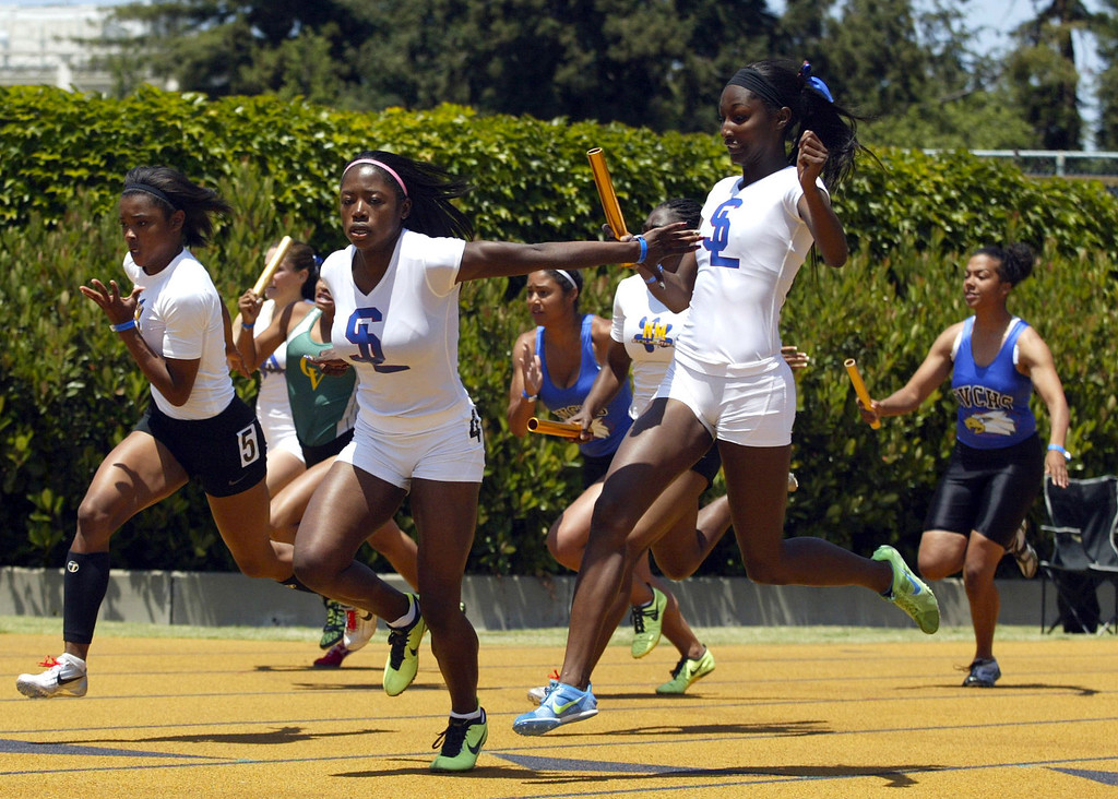 . San Leandro\'s Gabrielle Cantrell, left, takes the baton from teammate Nijae Jones, right, on the last leg of the girls 4x100 meter relay final at the North Coast Section Meet of Champions at Cal\'s Edwards Stadium in Berkeley, Calif., on Saturday, May 25, 2013. San Leandro placed first. (Anda Chu/Bay Area News Group)