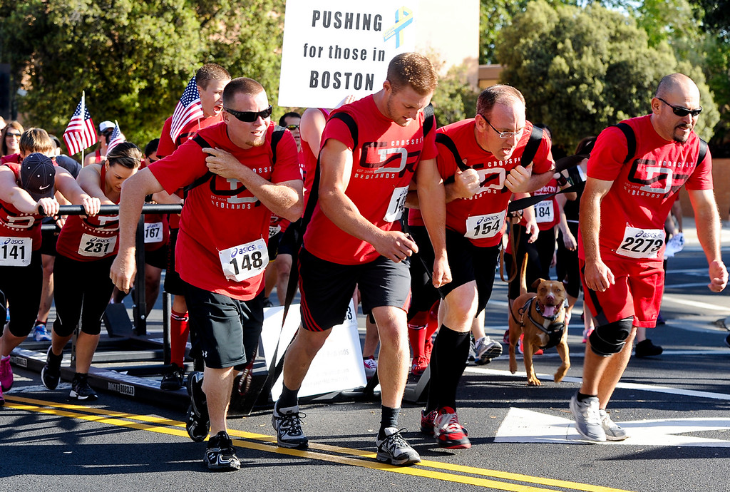 . A team of runners, representing Crossfit Redlands, pushes a  bobsled in honor of the Boston boming victims during the 30th annual Run Through Redlands race on Sunday, April 21, 2013. The race proceeds benefited the Kiwanis Club Foundation and scholarship opportunities for high school seniors. (Rachel Luna / Staff Photographer)