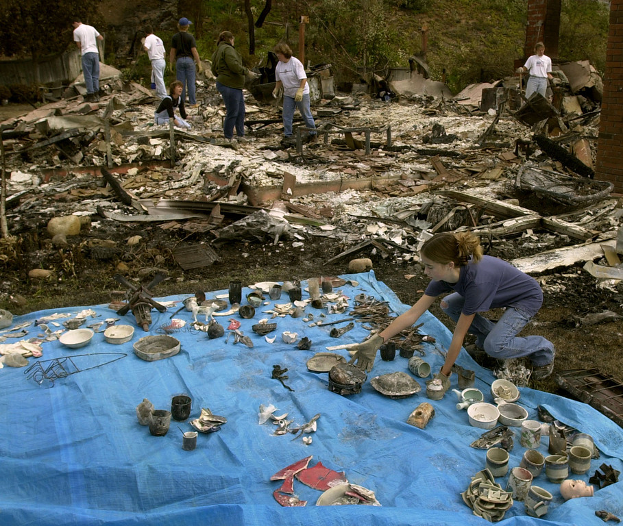 . Claire Shalinsky, 12, places items salvaged from her family\'s burned home in the Scripps Ranch area of San Diego, Calif. Thursday, Oct. 30, 2003. The home was among more than 1,400 lost in the 275,000 acre Cedar fire. (AP Photo/Charlie Riedel)