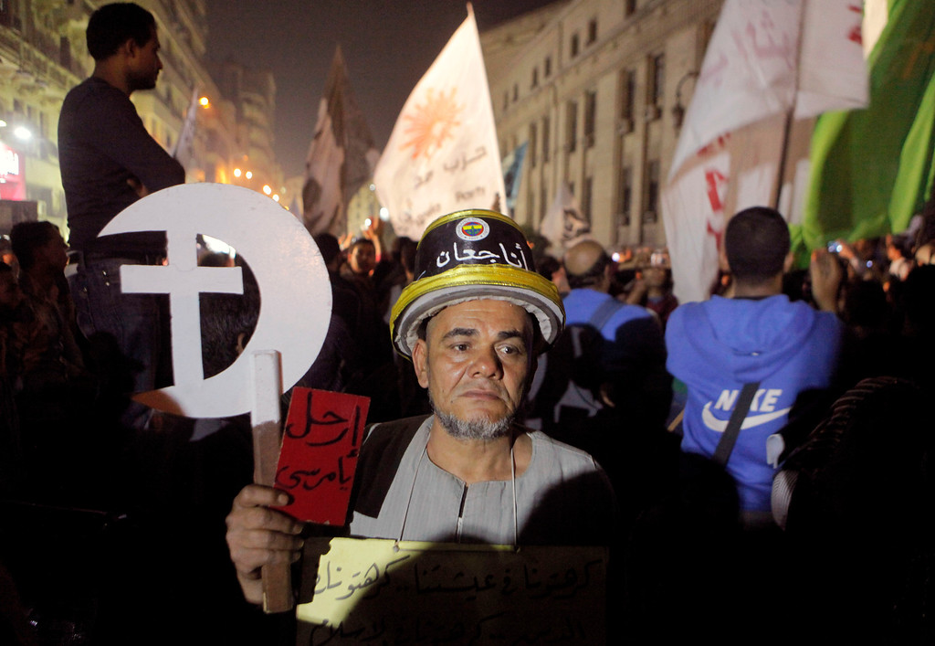 ". Egyptian Samir Mancy, 60, holds a red card with Arabic reading, ""Morsi step down\"", during a rally in front of the general prosecutor\'s office in Cairo, Egypt, Saturday, April 6, 2013. Arabic on the hat reads, \""I\'m hungry.\"" Thousands of activists took to the streets Saturday to mark the fifth anniversary of the founding of a leading opposition group, the April 6 Youth Movement, and to push a long list of demands, including the formation of a more inclusive government amid a worsening economy. (AP Photo/Amr Nabil)"