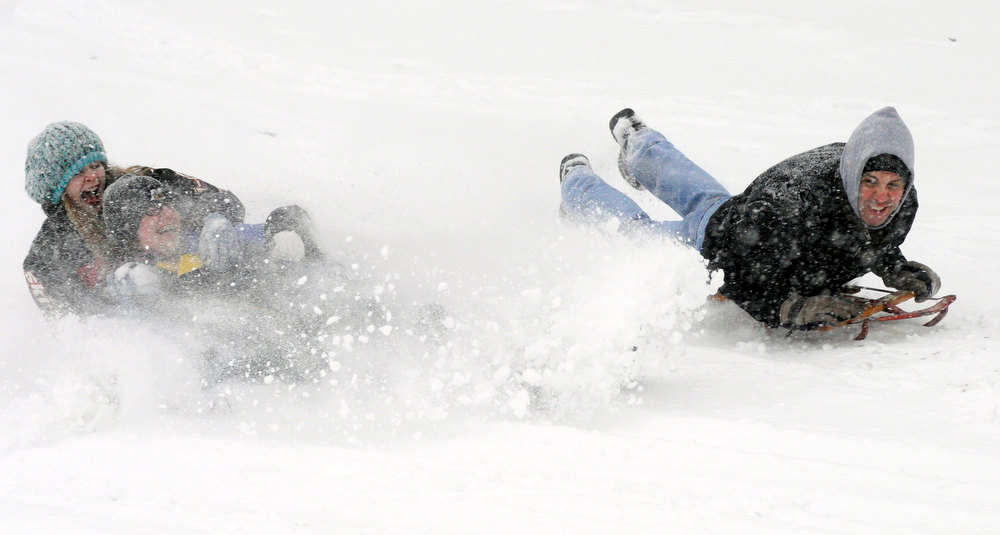 Description of . Ashley Scheibelhut and Summer Rose race Mike Hinshaw down the hill as they sled at the Country Club of Ashland in Ashland, Ohio, Wednesday, Dec. 26, 2012 during a snow storm. (AP Photo/Ashland Times-Gazette, Tom E. Puskar)