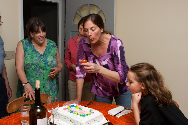 Lisa blows out the makeshift birthday cake candle.