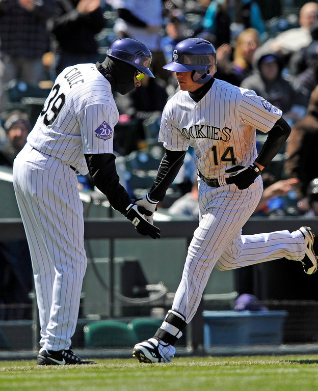 . Colorado Rockies\' Josh Rutledge (14) is congratulated by third base coach Stu Cole after hitting a home run off New York Mets starting pitcher Jonathon Niese during the fourth inning of a baseball game on Thursday, April 18, 2013, in Denver. (AP Photo/Jack Dempsey)