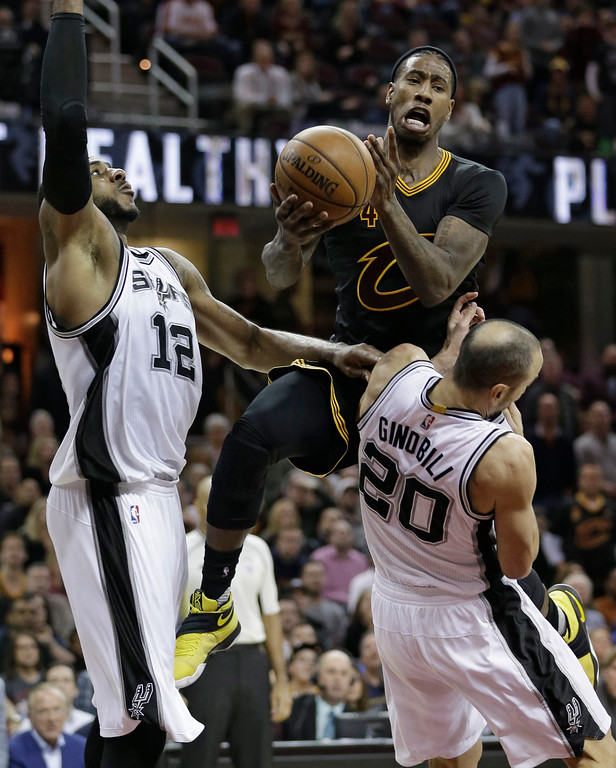 . Cleveland Cavaliers\' Iman Shumpert (4) is called for an offensive foul against San Antonio Spurs\' Manu Ginobili (20), from Argentina, during the second half of an NBA basketball game, Saturday, Jan. 21, 2017, in Cleveland. LaMarcus Aldridge (12) defends. The Spurs won 118-115 in overtime. (AP Photo/Tony Dejak)