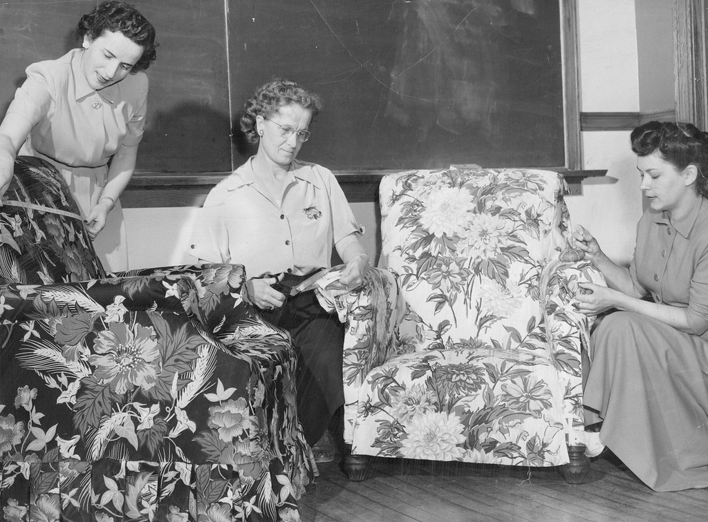 """. A new project is under way at Emily Griffith Opportunity school to teach Denver housewives to make professional looking slip covers and draperies in regular \""""learn by doing\"""" classes, held three times a week in 1950. In addition to renovating their own furniture members of the class have been adding a new look to the furniture of the school\'s faculty lounge. Shown left to right are three members of the class, Mrs. Sol Kruger,  Mrs. G. Miller and Mrs. Jene Sombar who are rejuvenating school furniture.  Credit: Denver Post"""