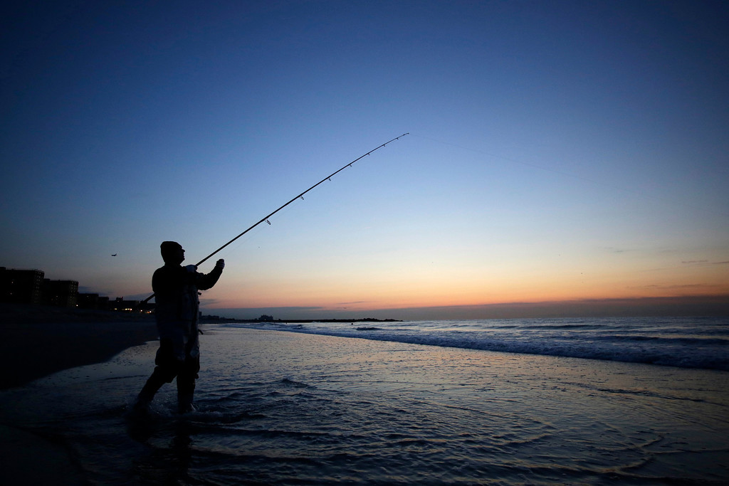 . A fisherman casts a line for striped bass on the beach in the Rockaways section of the Queens borough of New York, Tuesday, Oct. 29, 2013.  (AP Photo/Mark Lennihan)