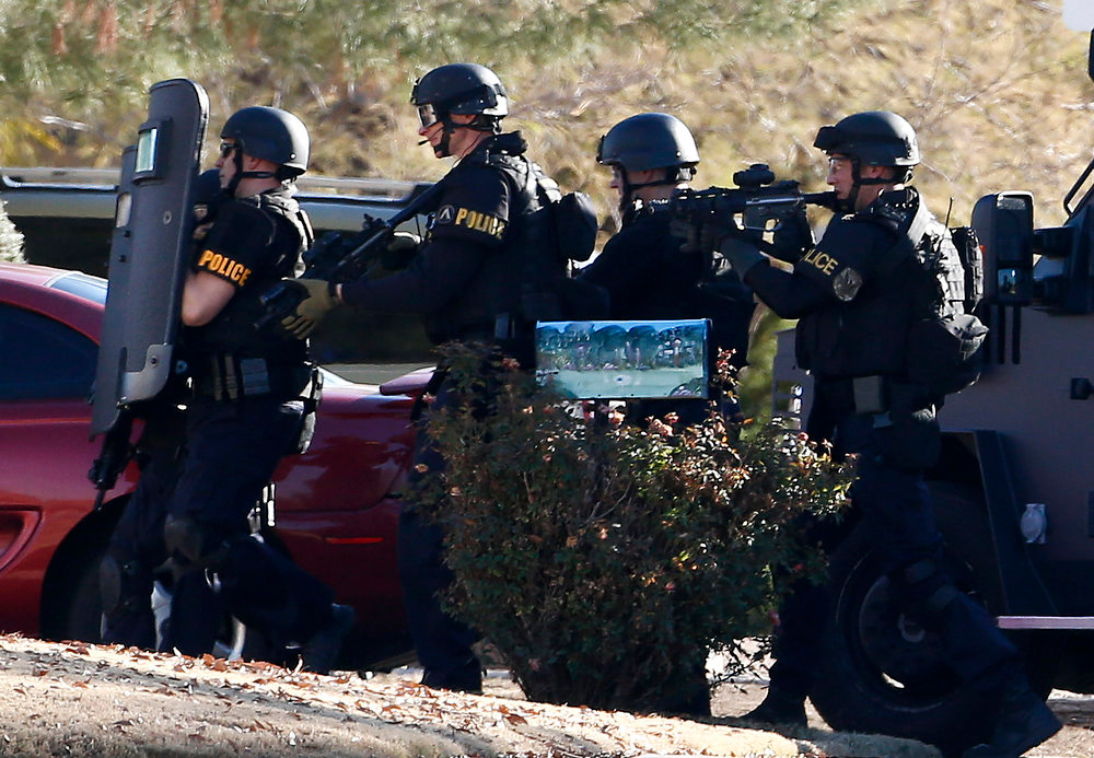 Description of . Members of the Phoenix Police Department SWAT team prepare to enter the home of a suspected gunman who opened fire at a Phoenix office building, wounding three people, one of them critically, and setting off a manhunt that led police to surround his house for several hours before they discovered he wasn't there, Wednesday, Jan. 30, 2013, in Phoenix. Authorities believe there was only one shooter, but have not identified him or a possible motive for the shooting. They don't believe the midmorning shooting at the complex was a random act. (AP Photo/Ross D. Franklin)
