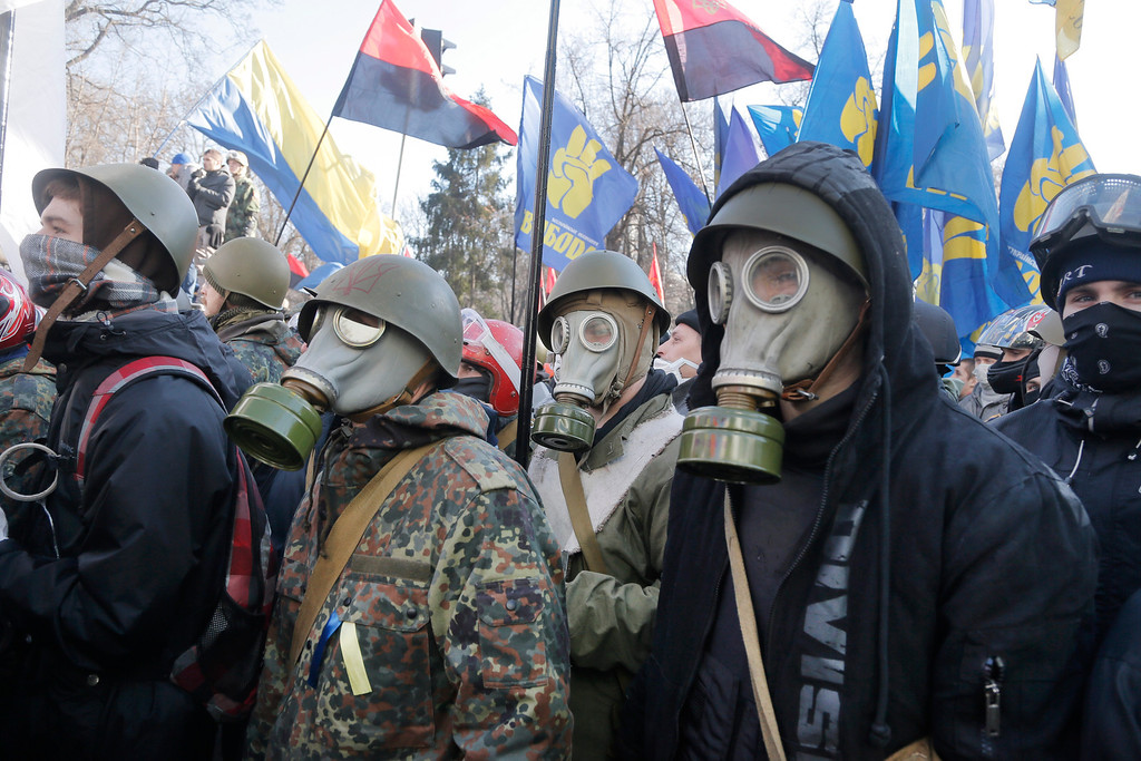 . Anti-government protesters look on during clashes with riot police outside Ukraine\'s parliament in Kiev, Ukraine, Tuesday, Feb. 18, 2014.  Some thousands of angry anti-government protesters clashed with police in a new eruption of violence Tuesday. (AP Photo/Efrem Lukatsky)