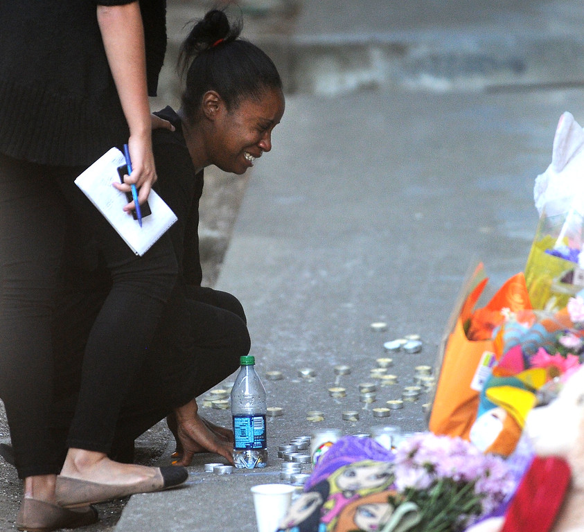 . Brea Colbert, looks at a makeshift memorial at the front door of her apartment in Oakland, Calif., on Saturday, July 20, 2013. Colbert\'s two children were shot and wounded and their friend Alaysha Carradine, 8, was killed when a gunman fired multiple shots into the apartment after Alaysha\'s friend opened the front door at 11:18 p.m. on Wednesday, July 17. No arrests have been made in the case. (Doug Duran/Bay Area News Group)