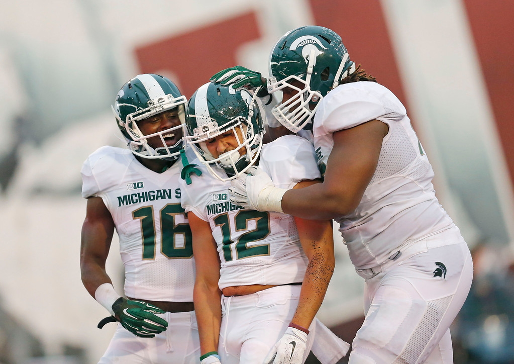 . Michigan State wide receiver Aaron Burbridge (16),  celebrates after Michigan State Spartans wide receiver R.J. Shelton (12) scored a touchdown in the second half of an NCAA college football game in Bloomington, Ind., Saturday, Oct. 18, 2014. At right is Michigan State ffensive lineman Donavon Clark (76). Michigan State won the game 56-17. (AP Photo/Sam Riche)