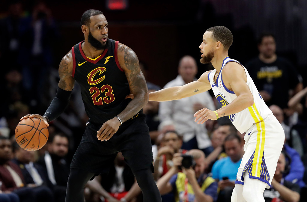 . Cleveland Cavaliers\' LeBron James is defended by Golden State Warriors\' Stephen Curry during the first half of Game 4 of basketball\'s NBA Finals, Friday, June 8, 2018, in Cleveland. (AP Photo/Tony Dejak)
