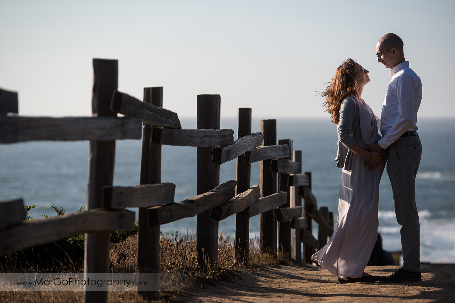 man pregnant woman in gray dress looking at each other at the Moss Beach during maternity session
