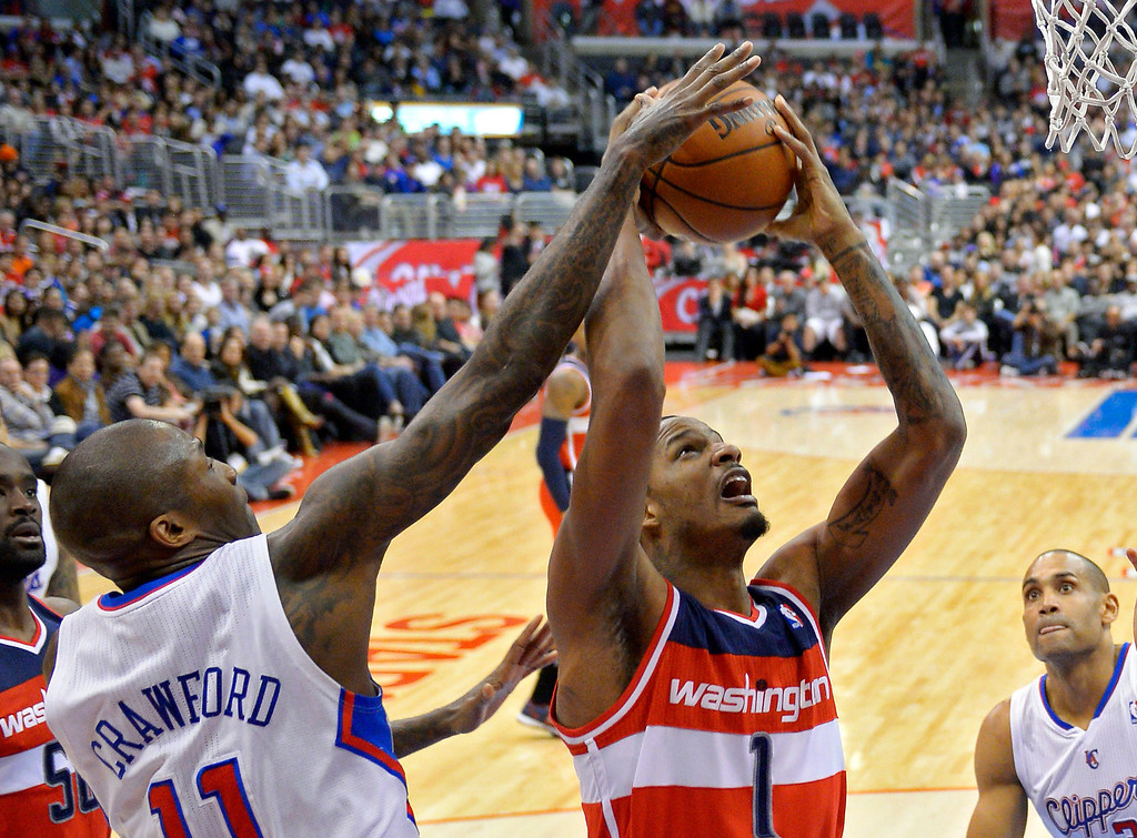 . Washington Wizards forward Trevor Ariza, center, puts up a shot as Los Angeles Clippers guard Jamal Crawford, left, defends and forward Grant Hill watches during the first half of their NBA basketball game, Saturday, Jan. 19, 2013, in Los Angeles.  (AP Photo/Mark J. Terrill)