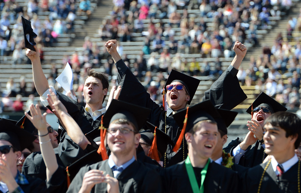 . New University of Colorado graduates respond to a video wrap up played during the ceremony. (Cliff Grassmick/Daily Camera)