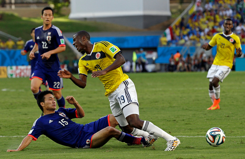 . Japan\'s Yasuyuki Konno fouls Colombia\'s Adrian Ramos to give away a penalty during the group C World Cup soccer match between Japan and Colombia at the Arena Pantanal in Cuiaba, Brazil, Tuesday, June 24, 2014. (AP Photo/Thanassis Stavrakis)