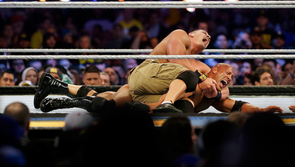 Description of . Wrestler John Cena, top, chokes Dwayne Douglas Johnson, known as The Rock as they wrestle Sunday, April 7, 2013, in East Rutherford, N.J., during Wrestlemania. (AP Photo/Mel Evans)