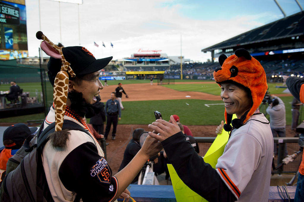 . Giants fans Jason Chow of Chapel Hill, NC and Ronald Leung of San Francisco entertain themselves before the start of Game 6 of the World Series at Kauffman Stadium in Kansas City, Mo on Tuesday, Oct. 28, 2014. (AP Photo/The Sacramento Bee, Jose Luis Villegas)