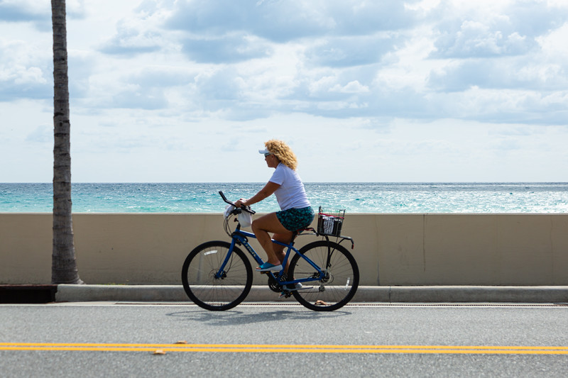 A woman rides her bicycle along N. Ocean Blvd., near the Palm Beach Country Club, April 23, 2020. [JOSEPH FORZANO/palmbeachdailynews.com]