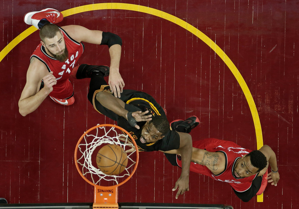 . Cleveland Cavaliers\' Tristan Thompson, center, drives to the basket against Toronto Raptors\' Jonas Valanciunas, left, from Lithuania, and Norman Powell in the first half of an NBA basketball game, Wednesday, April 12, 2017, in Cleveland. (AP Photo/Tony Dejak)