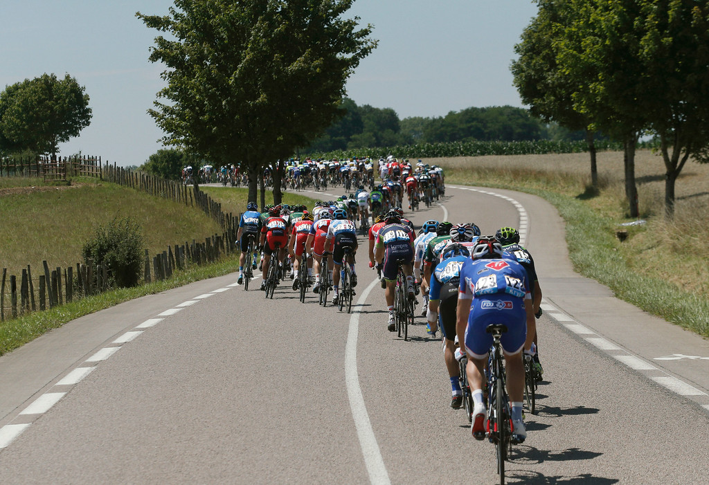 . The pack rides during the eleventh stage of the Tour de France cycling race over 187.5 kilometers (116.5 miles) with start in Besancon and finish in Oyonnax, France, Wednesday, July 16, 2014. (AP Photo/Christophe Ena)