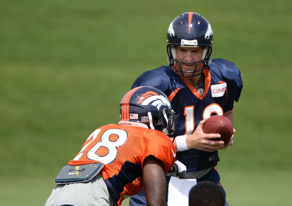 . Peyton Manning  of Denver Broncos (18) hands the ball to Montee Ball (28) during the Denver Broncos 2014 training camp at Dove Valley, Englewood, Colorado, August 01, 2014. (Photo by Hyoung Chang/The Denver Post)