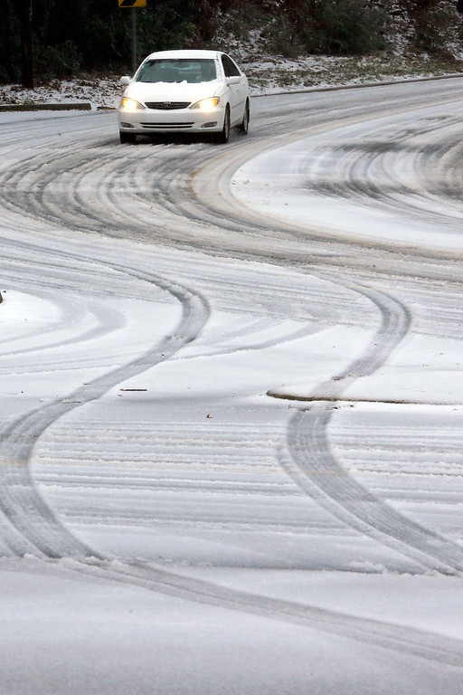 . A car makes its way down a sleet-covered hill in Little Rock, Ark., Friday, Dec. 6, 2013. Weather forecasters lifted an ice storm warning Friday for much of central Arkansas. (AP Photo/Danny Johnston)