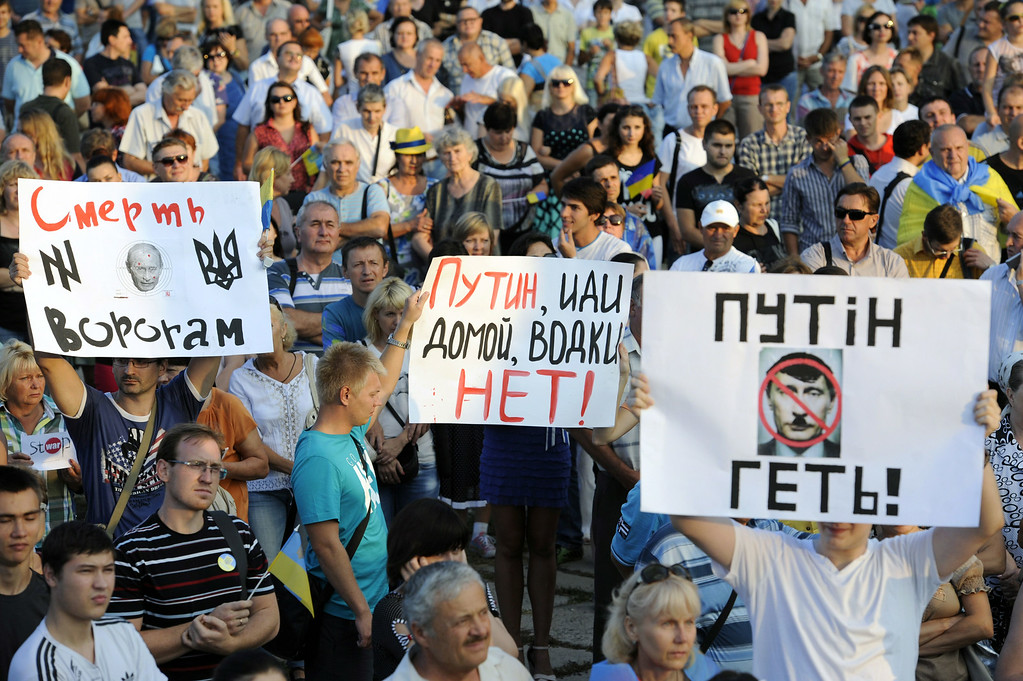 """. People hold placards (RtoL) reading \""""Putin get out!\"""", \""""Putin go home, there is no vodka!\"""" and \""""Death for enemies!\"""", during a rally in the center of the southern Ukrainian city of Mariupol, in the Donetsk region, on August 28, 2014. A few thousand people called for a united Ukraine and asked for Russia to  withdraw its military forces from the country. Alexander KHUDOTEPLY/AFP/Getty Images"""