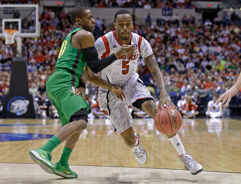 . Louisville guard Kevin Ware (5) drives against Oregon guard Johnathan Loyd (10) during the first half of a regional semifinal in the NCAA college basketball tournament, Friday, March 29, 2013, in Indianapolis. (AP Photo/Michael Conroy)