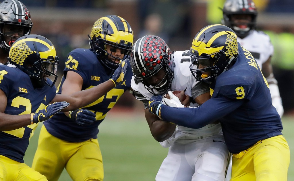 . Ohio State quarterback J.T. Barrett (16) is stopped by Michigan linebacker Mike McCray (9) during the first half of an NCAA college football game, Saturday, Nov. 25, 2017, in Ann Arbor, Mich. (AP Photo/Carlos Osorio)