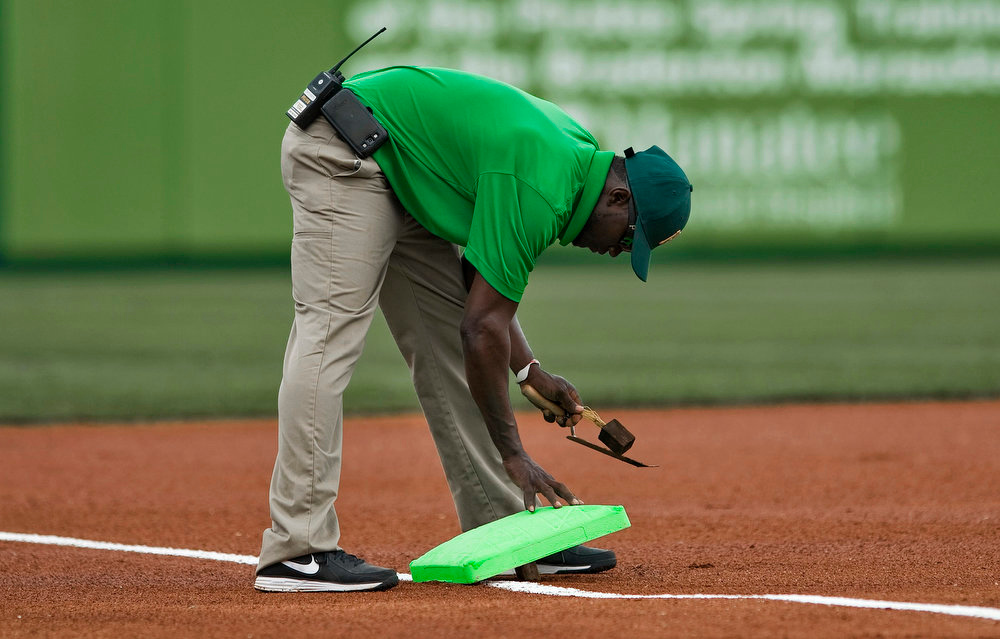 . A Pittsburgh Pirates ground crew worker installs green bases in honor of St. Patrick\'s Day before the start of a MLB spring training baseball game with the New York Yankees in Bradenton, Florida, March 17, 2013.  REUTERS/Steve Nesius