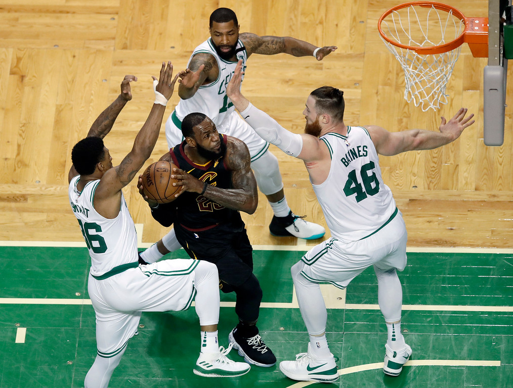 . Cleveland Cavaliers forward LeBron James, center, drives through the defense of Boston Celtics guard Marcus Smart, left, forward Marcus Morris, rear, and center Aron Baynes, right, during the first half in Game 7 of the NBA basketball Eastern Conference finals, Sunday, May 27, 2018, in Boston. (AP Photo/Charles Krupa)