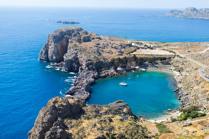A blue ocean harbor surrounded by rocky land in Rhodes.