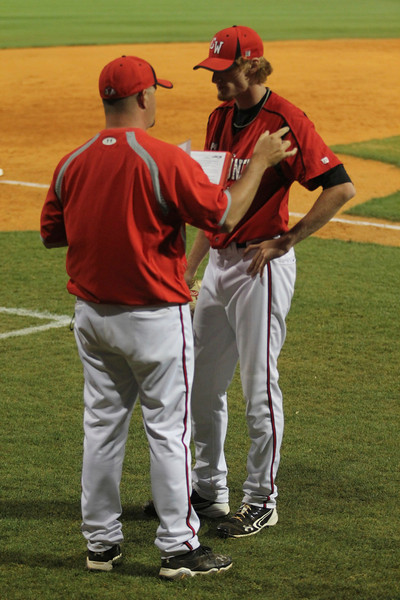 Coach talks to number 37, Adam Izokovic, in between innings.