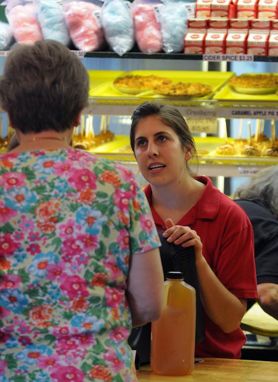 . Lisa Palaian of Rochester Hills waits on a customer at Yates cider mill. (The Macomb Daily/DAVID DALTON)