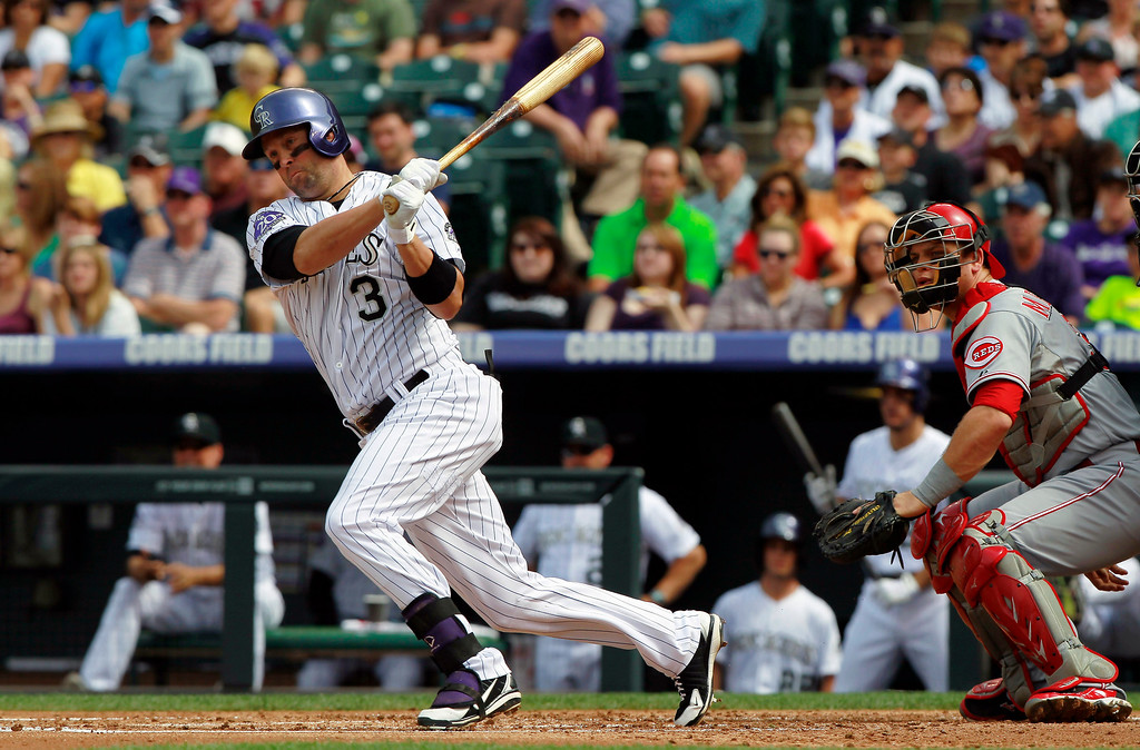 . Colorado Rockies\' Michael Cuddyer, left, follows the flight of his RBI-double with Cincinnati Reds catcher Devin Mesorao, right, in the first inning of a baseball game in Denver, Sunday, Sept. 1, 2013. (AP Photo/David Zalubowski)