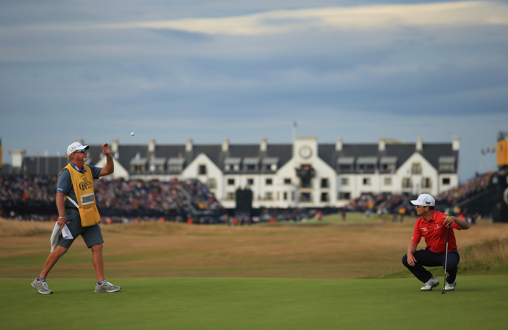 . Zach Johnson of the US throws a ball to his caddie on the 17th green during the third round of the British Open Golf Championship in Carnoustie, Scotland, Saturday July 21, 2018. (AP Photo/Jon Super)