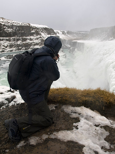 """Gullfoss (Golden Falls) is a massive waterfall located in the canyon of Hvítá river in southwest Iceland.  It is is one of the most popular tourist attractions in the country. The wide Hvítá rushes southward and 1km above the falls it turns sharply to the left and flows down into a wide curved three-step """"staircase"""" and then abruptly plunges in two stages into a crevice 105 ft deep. The crevice is 60 ft wide, and 2.5 km in length, is at right angles to the flow of the river.   The part frozen falls took my breath away as I first approached. Spectacular is just not grand enough to describe it. I trust the pictures help. Me getting very close to the edge! Olympus E510 in action. Olympus E510, 14-42mm."""