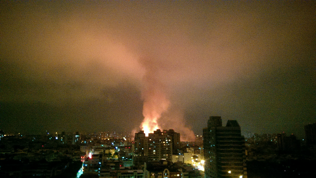 . Smoke and flames from an explosion from an underground gas leak rise above the streets of Kaohsiung, Taiwan, early Friday, Aug. 1, 2014.  A massive gas leakage early Friday caused five explosions that killed several people and injured over 200 in the southern Taiwan port city of Kaohsiung. (AP Photo/Tsun Zheng Hao)