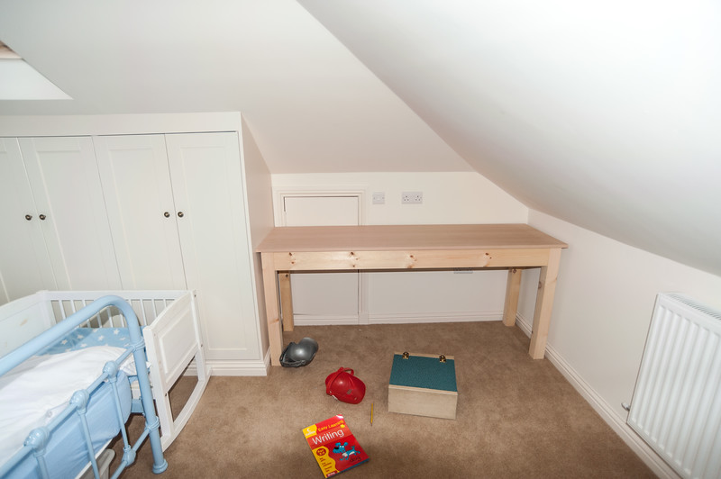 Wardrobs following the shape of attic room, plus work table