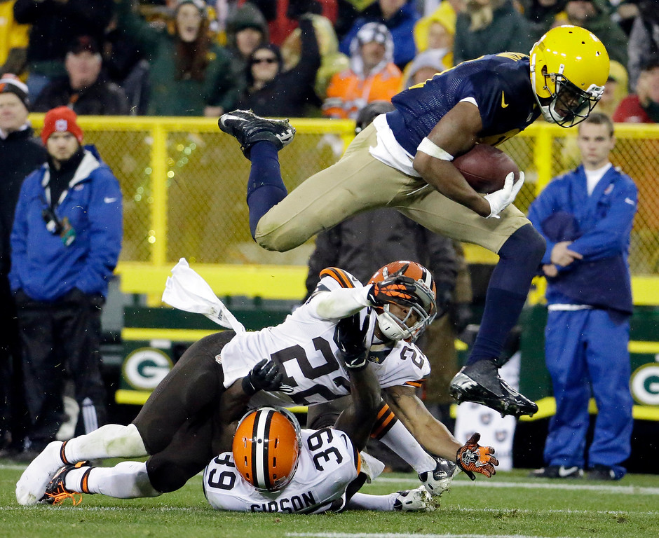 . Green Bay Packers\' Jarrett Boykin leaps over Cleveland Browns\' Buster Skrine (22) and Tashaun Gipson (39) after a catch during the second half of an NFL football game Sunday, Oct. 20, 2013, in Green Bay, Wis. (AP Photo/Morry Gash)