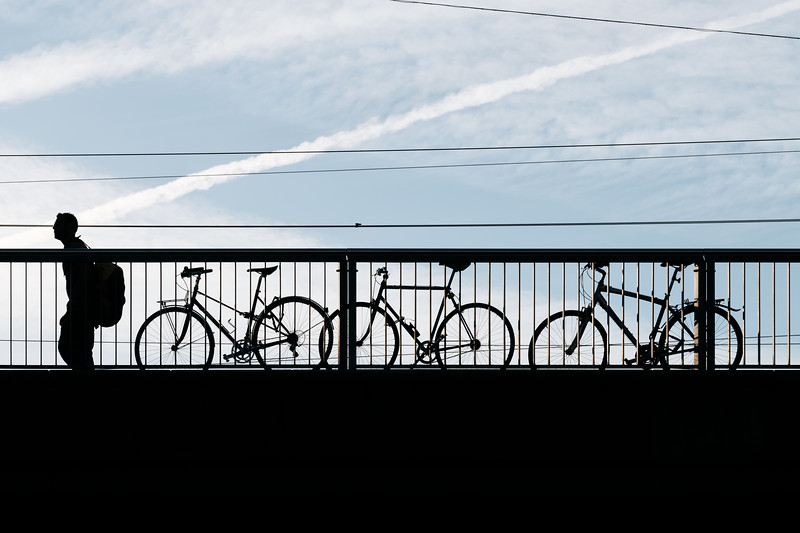 Silhouette of a man walking with bicycles