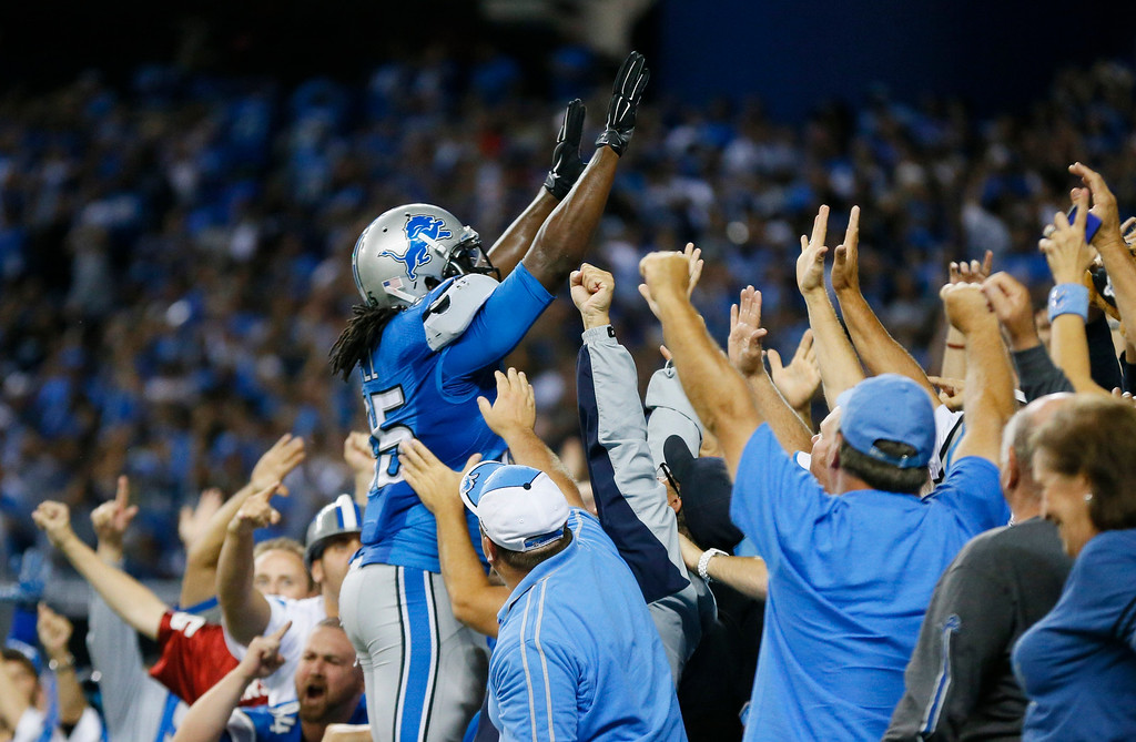 . Detroit Lions running back Joique Bell celebrates with fans after scoring during the fourth quarter of an NFL football game against the New York Giants in Detroit, Monday, Sept. 8, 2014. (AP Photo/Paul Sancya)