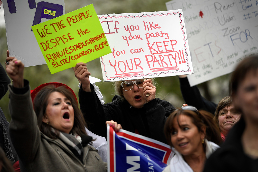 . Denver, CO - ARRIL 15: Cheron Owen of Denver cheers with her two signs as Colorado Republican voters gather at the state Capitol to protest the delegate selection process when the GOP officials decided not to hold a straw poll March 1st and denied them their vote. April 15, 2016 in Denver, CO. (Photo By Joe Amon/The Denver Post)