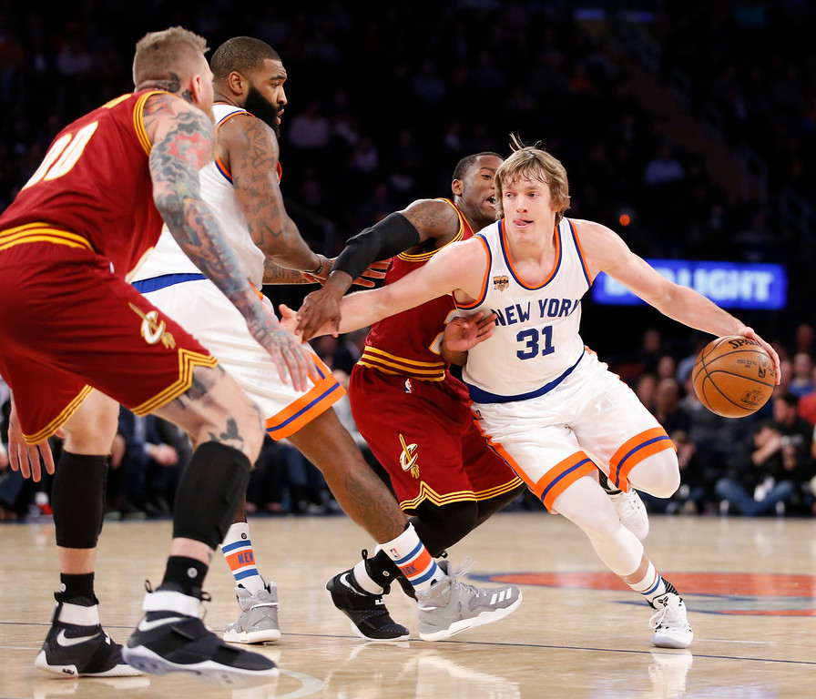 . New York Knicks guard Ron Baker (31) drives around Cleveland Cavaliers guard Kay Felder, second from right, in the second half of an NBA basketball game at Madison Square Garden in New York, Wednesday, Dec. 7, 2016. The Cavaliers defeated the Knicks 126-94. New York Knicks center Kyle O\'Quinn (9) backs up Baker as Cleveland Cavaliers forward Chris Andersen, far left, defends. (AP Photo/Kathy Willens)