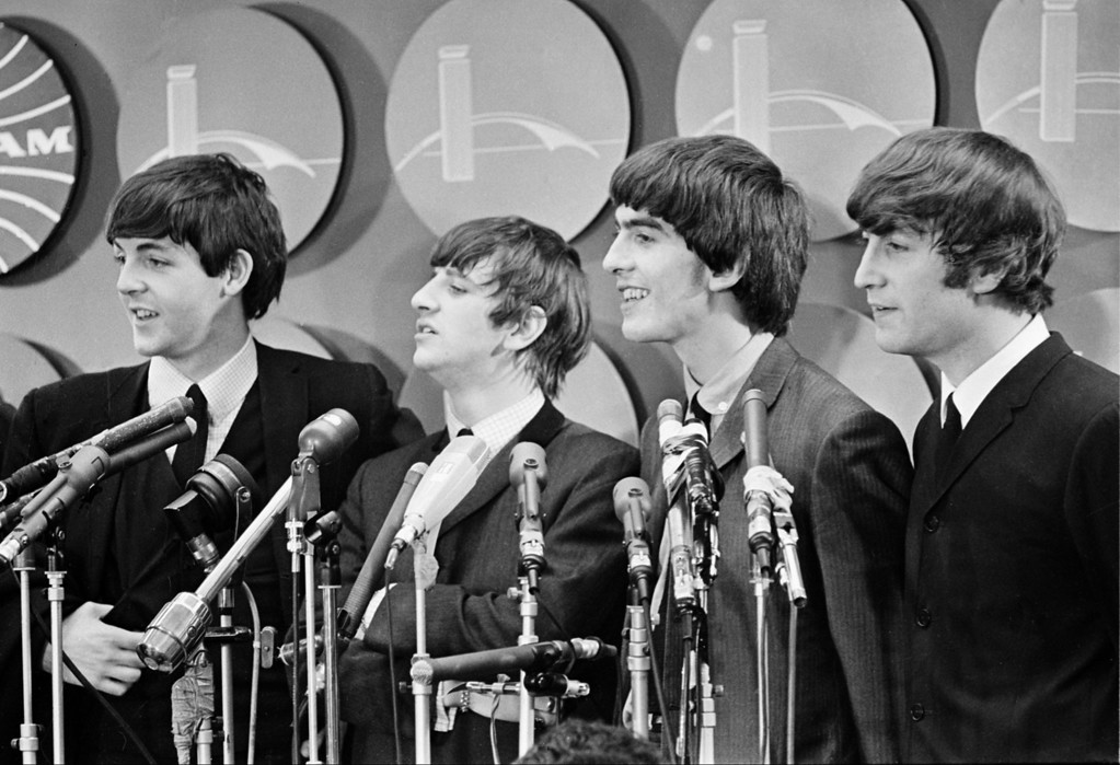 . The Beatles meet reporters at Kennedy Airport in New York City, Feb. 7, 1964 on their arrival from London for their first American tour.  The band members, from left, are, Paul McCartney, Ringo Starr, George Harrison, and John Lennon.  (AP Photo)