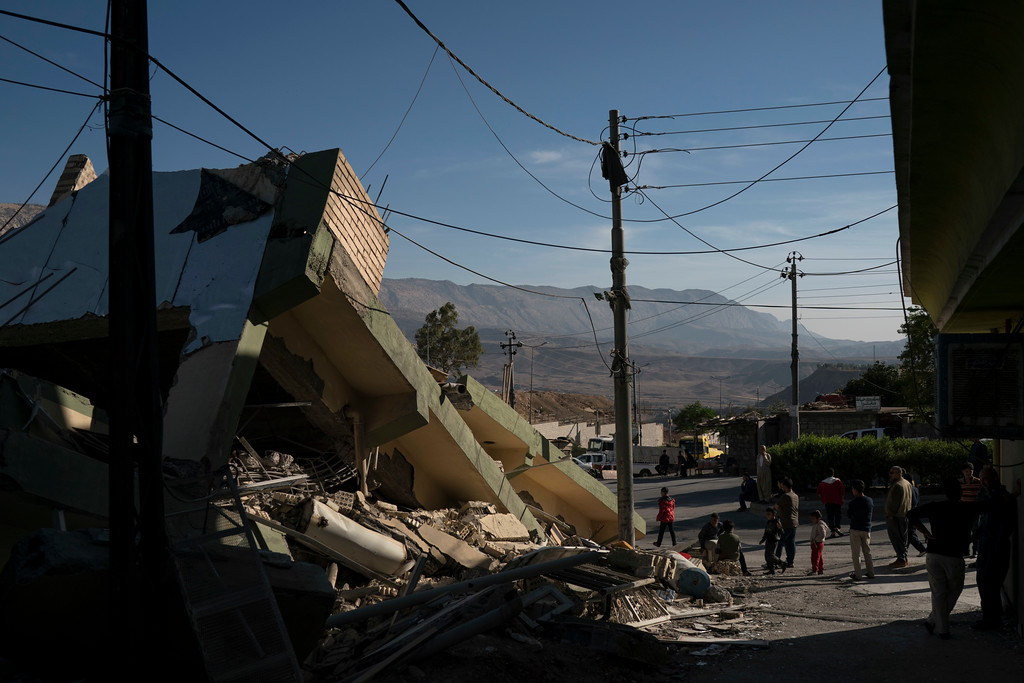 . People walk next to a destroyed house after an earthquake in the city of Darbandikhan, northern Iraq, Monday, Nov. 13, 2017. Authorities reported that a powerful 7.3 magnitude earthquake struck the Iraq-Iran border region on Monday and killed more than three hundred people in both countries, sent people fleeing their homes into the night and was felt far west as the Mediterranean coast. (AP Photo/Felipe Dana)