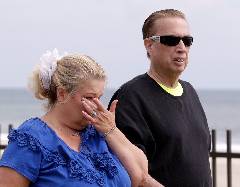 . Julie Migliorisi, left, of Seaside Heights, N.J., wipes tears off her face while walking with her husband Richard Migliorisi moments after the couple met with New Jersey Gov. Chris Christie, who visited the area hit by a massive fire a day earlier, Friday, Sept. 13, 2013, in Seaside Park, N.J. The fire, which apparently started in an ice cream shop and spread several blocks, hit the recently repaired boardwalk, which was damaged last year by Superstorm Sandy. There were no reports of any injuries. The Migliorisis were displaced from their home when Sandy ripped through the region and have been living in Bergen County while their home is repaired. (AP Photo/Julio Cortez)