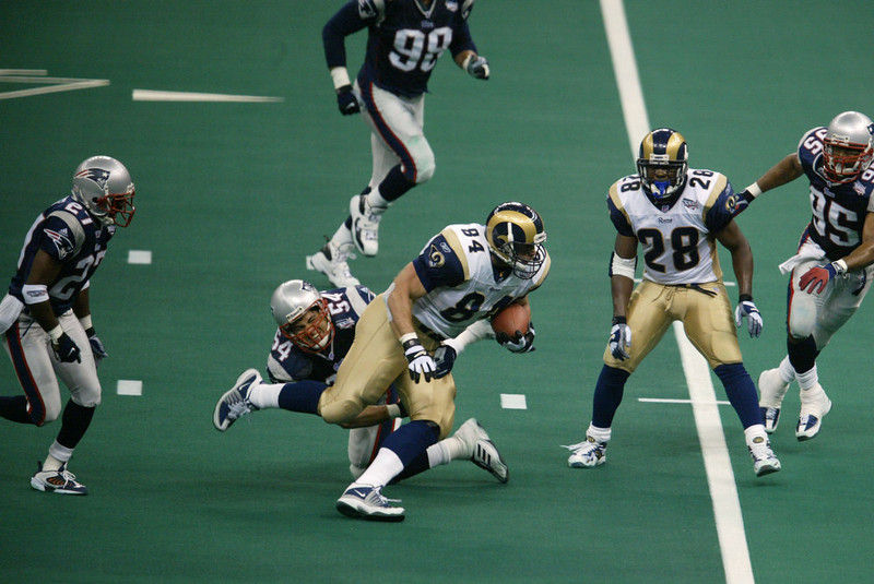 . 03 Feb 2002:   Ernie Conwell #84 of the St.Louis Rams breaks through a tackle attempt by Tedy Bruschi #54 of the New England Patriots during Superbowl XXXVI at the Superdome in New Orleans, Louisiana.  The Patriots defeated the Rams 20-17. Al Bello/Getty Images