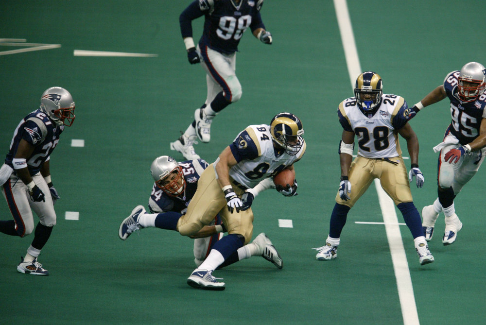 Description of . 03 Feb 2002:   Ernie Conwell #84 of the St.Louis Rams breaks through a tackle attempt by Tedy Bruschi #54 of the New England Patriots during Superbowl XXXVI at the Superdome in New Orleans, Louisiana.  The Patriots defeated the Rams 20-17. Al Bello/Getty Images