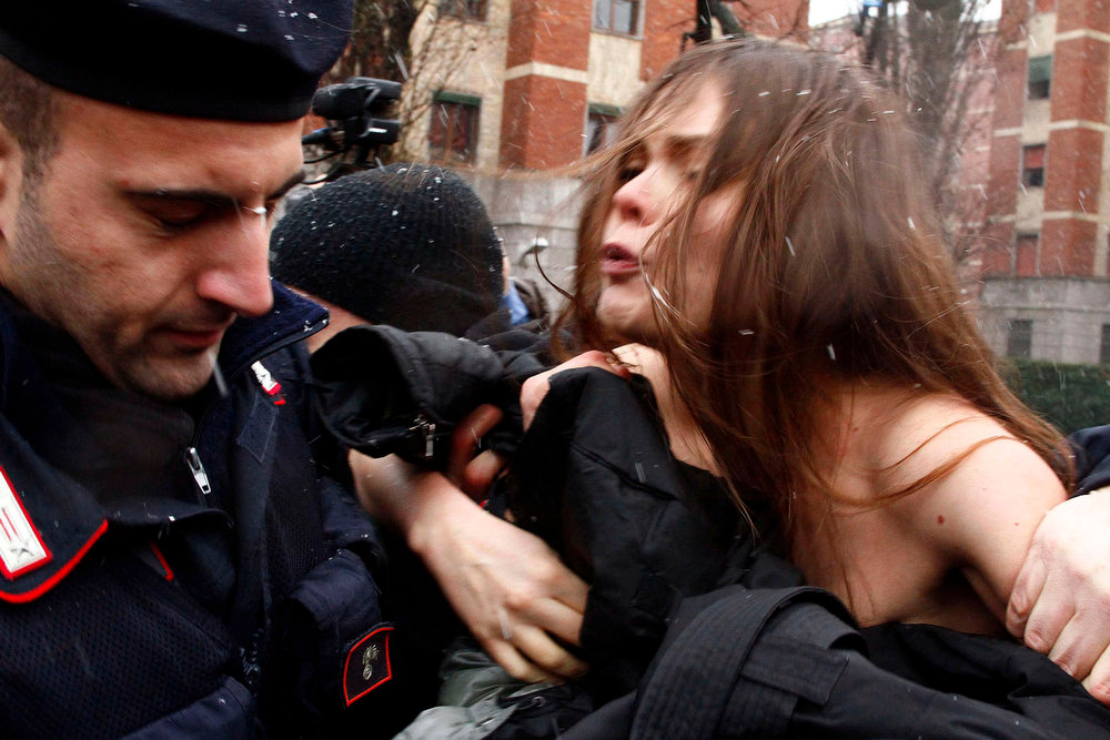 ". Police detain a woman protesting, as former Italian Premier Silvio Berlusconi voted, in Milan, Italy, Sunday, Feb. 24, 2013.  Three women reportedly from the feminist group ""Femen\"" attempted to disrupt former premier Silvio Berlusconi as he voted in the Italian elections on Sunday. The activists pulled off their sweaters to bare their breasts and display the slogan \""Basta Silvio!\"" (Enough of Silvio) written on their body as Berlusconi entered the polling station in Milan. A cordon of police, already in place for security before the former premier\'s arrival, blocked Berlusconi\'s direct view of the women. (AP Photo/Spada, Lapresse)"